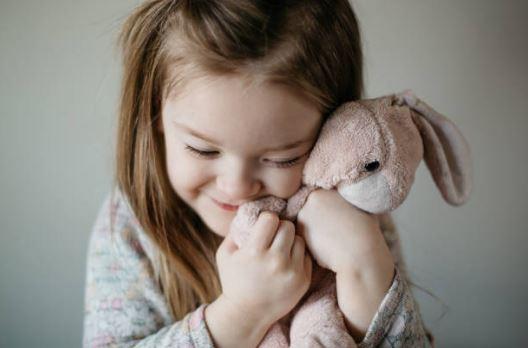 Petite fille qui câline son doudou lapin