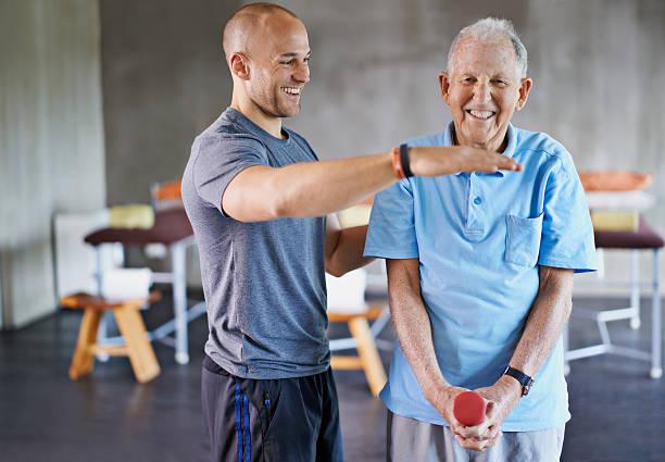 Kinésithérapeute qui accompagne une personne âgée souffrant d'arthrose