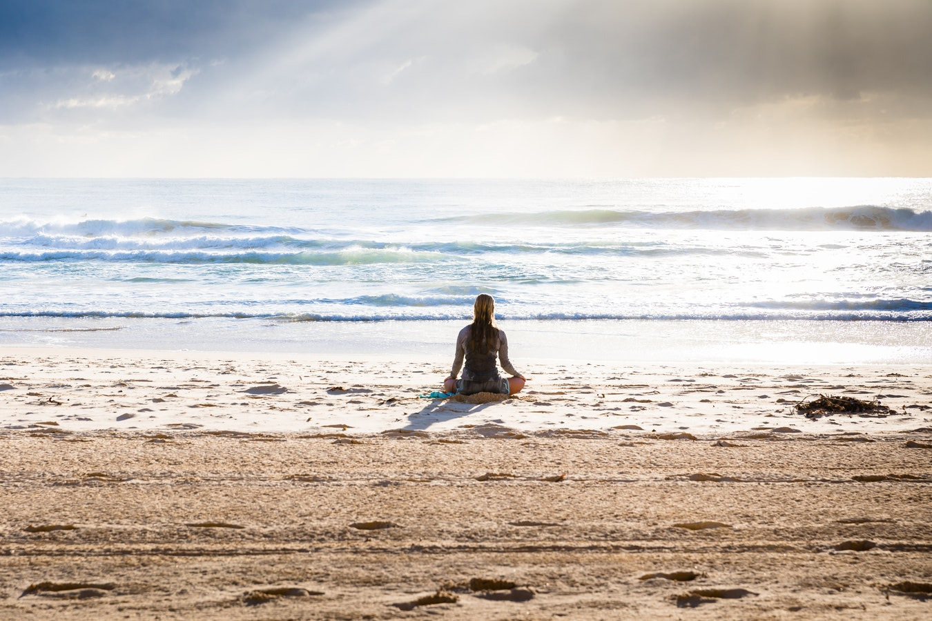 Voyageuse en pleine méditation dans la posture du lotus au bord de la mer