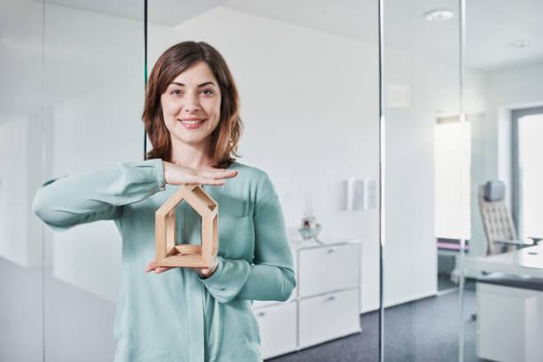 Femme qui sourie à la caméra avec une maison en bois dans les mains
