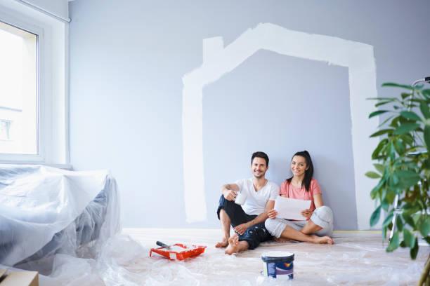 Un couple assis au milieu d'une pièce en pleine rénovation
