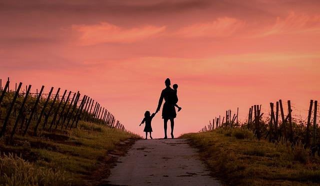 mère avec ses enfants au bout d'un chemin avec couchée de soleil